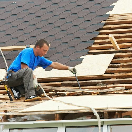 A Roofer Works On a Roof Replacement.