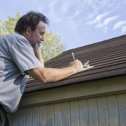 An Insurance Adjuster Works on a Roof Insurance Claim.