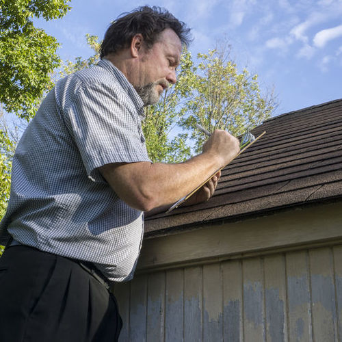 An Insurance Adjuster on Ladder Checks for Roof Leaks.