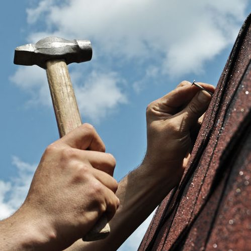 Close Up of Hand Hammering Nails into Roofing Material