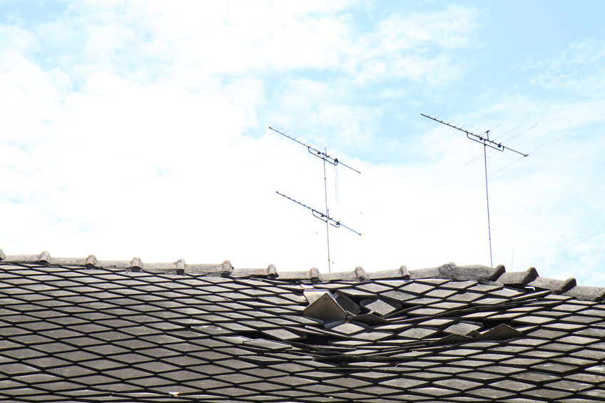 Broken Roof With Collapsed Shingles and a Background of a Blue Sky